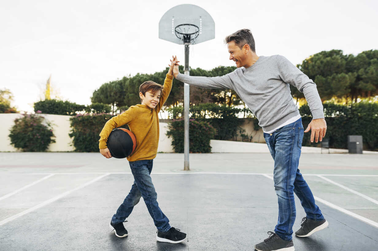 Father and son high fiving on basketball outdoor court - EBSF02070 - Bonninstudio/Westend61