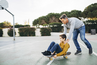 Father assisting son riding skateboard - EBSF02073