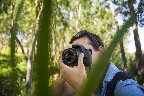 Man taking photos in forest - ZEF14935