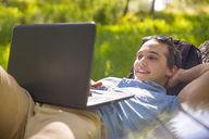 Portrait of happy young man lying on tree trunk in nature using laptop - ZEF14944