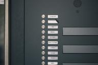 Doorbell button panel with empty nameplate of deceased neighbour - MF04386