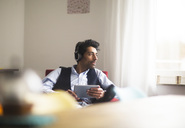 Portrait of pensive man with headphones and tablet sitting on armchair looking out of window - SGF02148