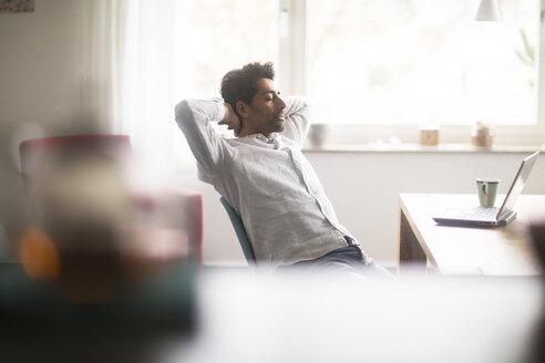 Businessman relaxing at desk - SGF02151