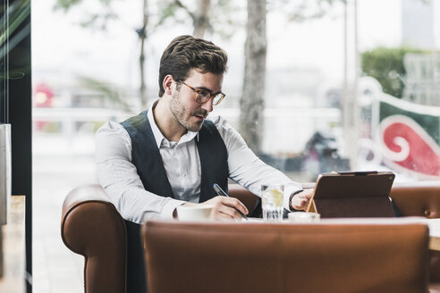 Young man working in a cafe using tablet and taking notes - UUF12597
