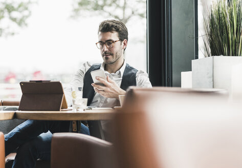 Young man working in a cafe using tablet and cell phone - UUF12603