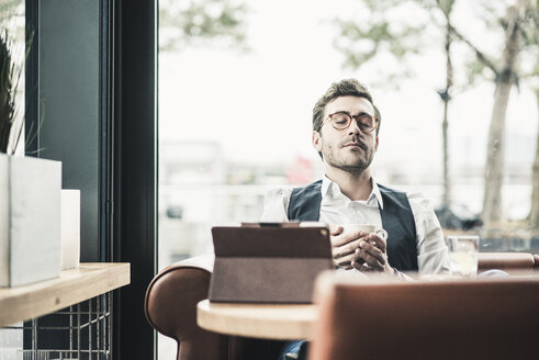 Young man in a cafe with tablet cup of coffee relaxing - UUF12609