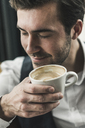 Relaxed young man drinking cup of coffee - UUF12618