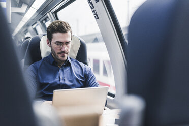 Businessman working in train using laptop - UUF12630