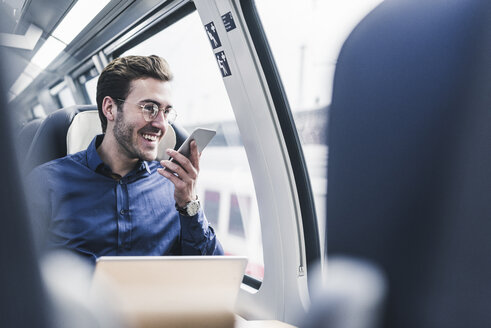 Happy businessman in train using cell phone - UUF12633