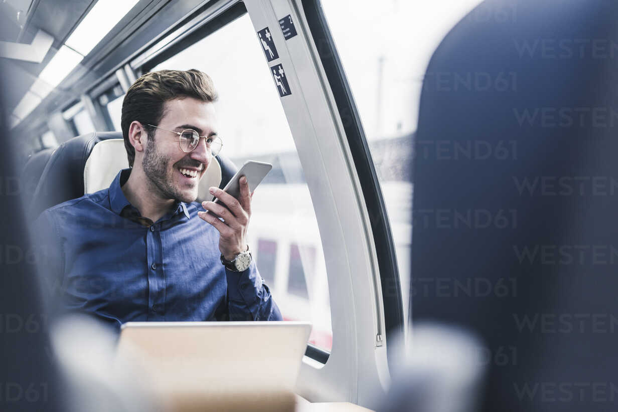 Happy businessman in train using cell phone - UUF12633 - Uwe Umstätter/Westend61