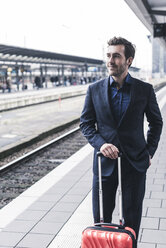 Young businessman waiting at station platform - UUF12636