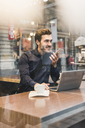 Smiling young businessman in a cafe at train station with cell phone and laptop - UUF12639