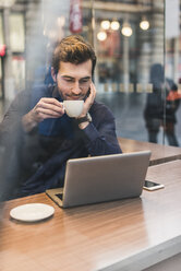 Young businessman in a cafe at train station with cup of coffee and laptop - UUF12642