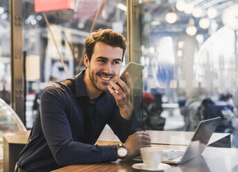 Smiling young businessman in a cafe at train station with cell phone and laptop - UUF12645