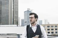 Germany, Frankfurt, young businessman with cell phone in the city looking around - UUF12648