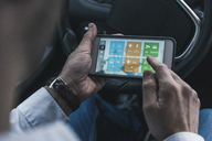Man in car adjusting devices at home via smartphone - UUF12651