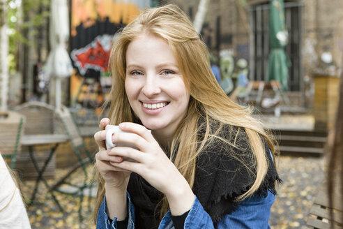 Germany, Berlin, portrait of happy young woman drinking coffee in sidewalk cafe - OJF00243