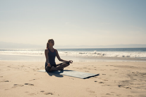 Young woman exercising yoga at a beach - ABAF02198