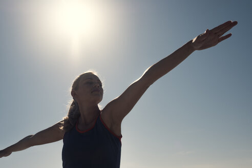Young woman exercising yoga under blue sky in backlight - ABAF02201