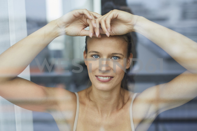 Portrait of smiling young woman behind windowpane - PNEF00408