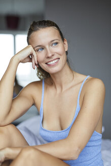Portrait of happy young woman sitting on bed - PNEF00411