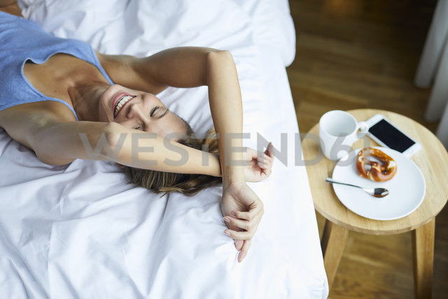 Laughing young woman lying in bed - PNEF00414