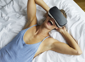 Laughing young woman lying in bed wearing VR glasses - PNEF00417