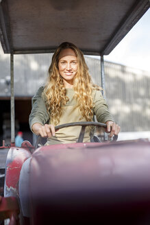 Portrait of smiling woman driving a tractor - PESF00899