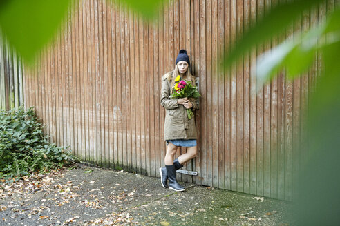 Portrait of young woman standing at wooden wall holding bunch of flowers - PESF00902