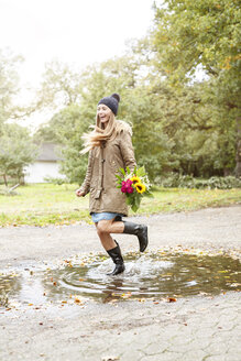 Happy young woman holding bunch of flowers jumping in puddle - PESF00905