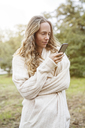Blond woman in rural landscape looking at cell phone - PESF00908