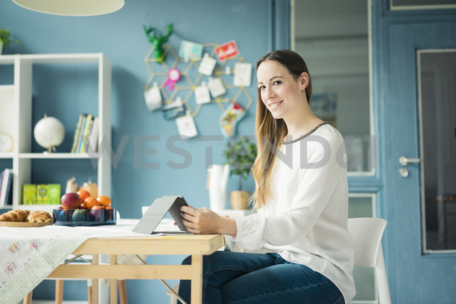 Portrait of smiling woman using tablet at breakfast table - MOEF00709 - Robijn Page/Westend61