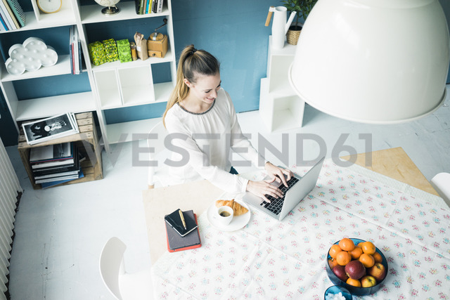 Smiling woman working on laptop at home - MOEF00721