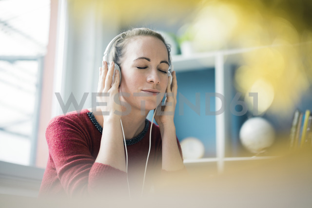 Portrait of woman with eyes closed  listening music with headphones - MOEF00724