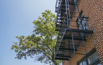 USA, New York, Brooklyn, Close up of fire escape over red brick facade - DAPF00869