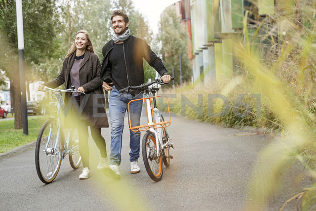Smiling couple walking with bicycles on a lane - PESF00914 - Peter Scholl/Westend61