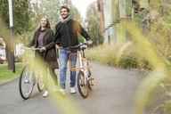 Smiling couple walking with bicycles on a lane - PESF00914