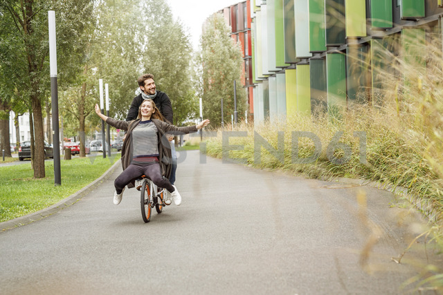 Happy couple riding on one bicycle on a lane - PESF00917 - Peter Scholl/Westend61