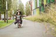 Happy couple riding on one bicycle on a lane - PESF00917