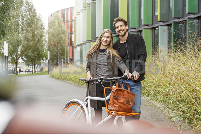 Portrait of smiling couple with bicycle on a lane - PESF00920 - Peter Scholl/Westend61