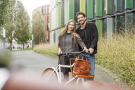 Portrait of smiling couple with bicycle on a lane - PESF00920