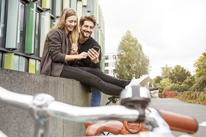 Happy couple with bicycles sitting on a wall looking at cell phone - PESF00926