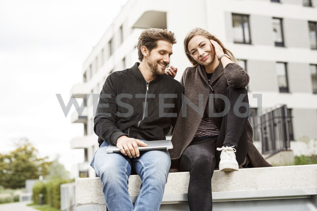 Happy couple with laptop in urban surrounding - PESF00932 - Peter Scholl/Westend61