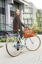 Smiling woman with bicycle standing in front of a building - PESF00935