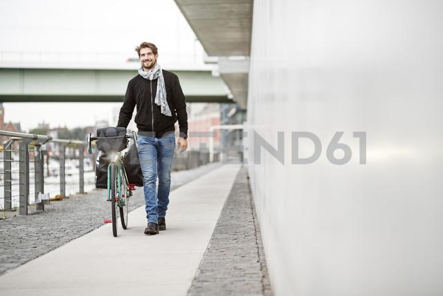 Smiling man pushing bicycle on a path - PESF00938