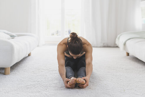 Woman sitting on the floor practicing yoga - ASCF00788