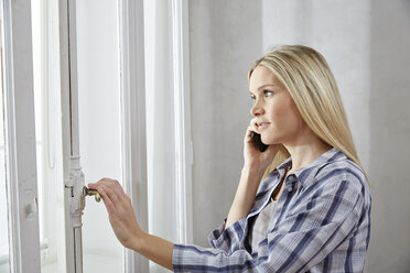 Blond woman on the phone looking out of window - FMKF04743