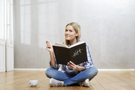 Portrait of smiling blond woman with book sitting on the floor - FMKF04746