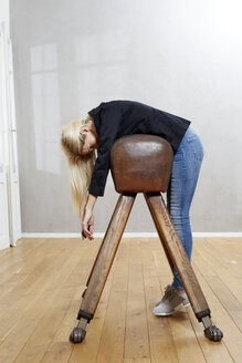 Woman leaning on pommel horse - FMKF04749