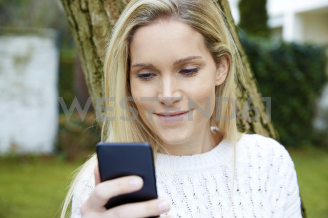 Portrait of smiling blond woman looking at cell phone outdoors - FMKF04752 - Jo Kirchherr/Westend61